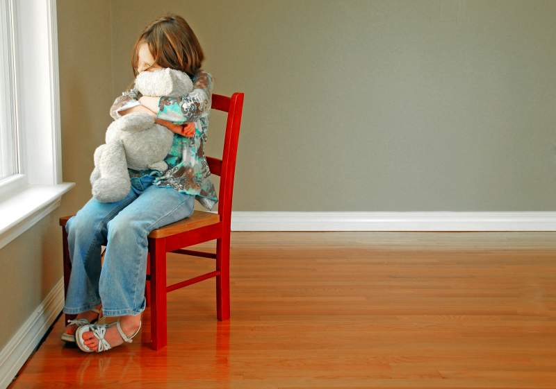 A girl sitting on a red chair with a teddy bear in her lap. The room is empty and the girl is sitting by the window.