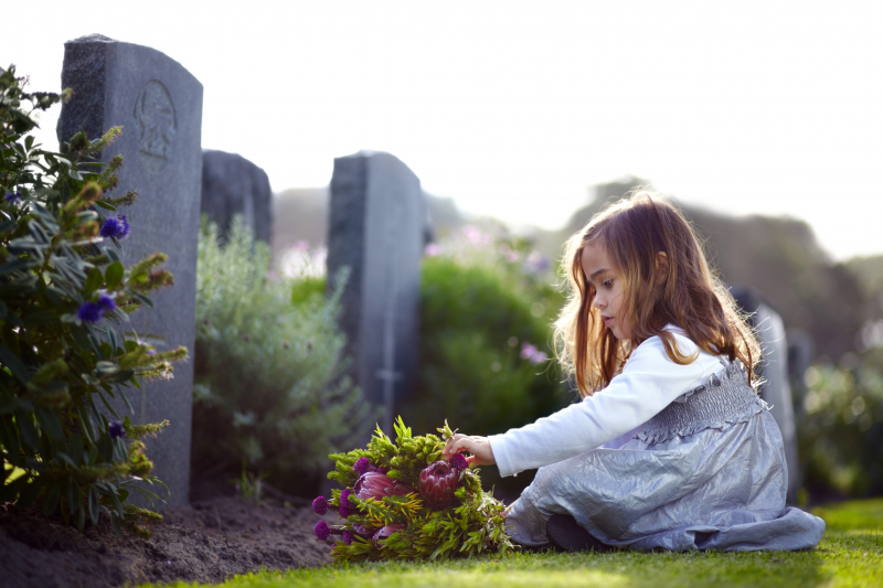 A small girl sitting in front of a gravestone.